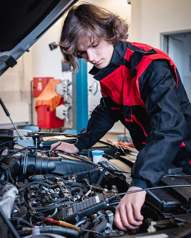 student opravuje auto